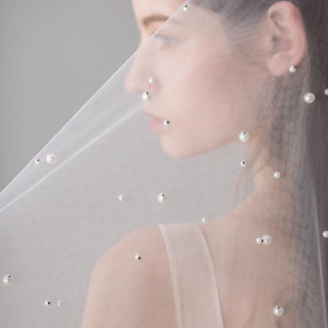 Velo de tul con aplicaciones de perlas bordadas a mano detalle